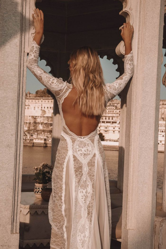 Back shot of bride wearing Grace Loves Lace Inca Gown leaning against stone archway