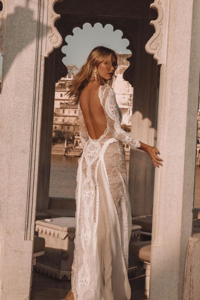 Back shot of bride wearing Grace Loves Lace Inca Gown holding stone archway