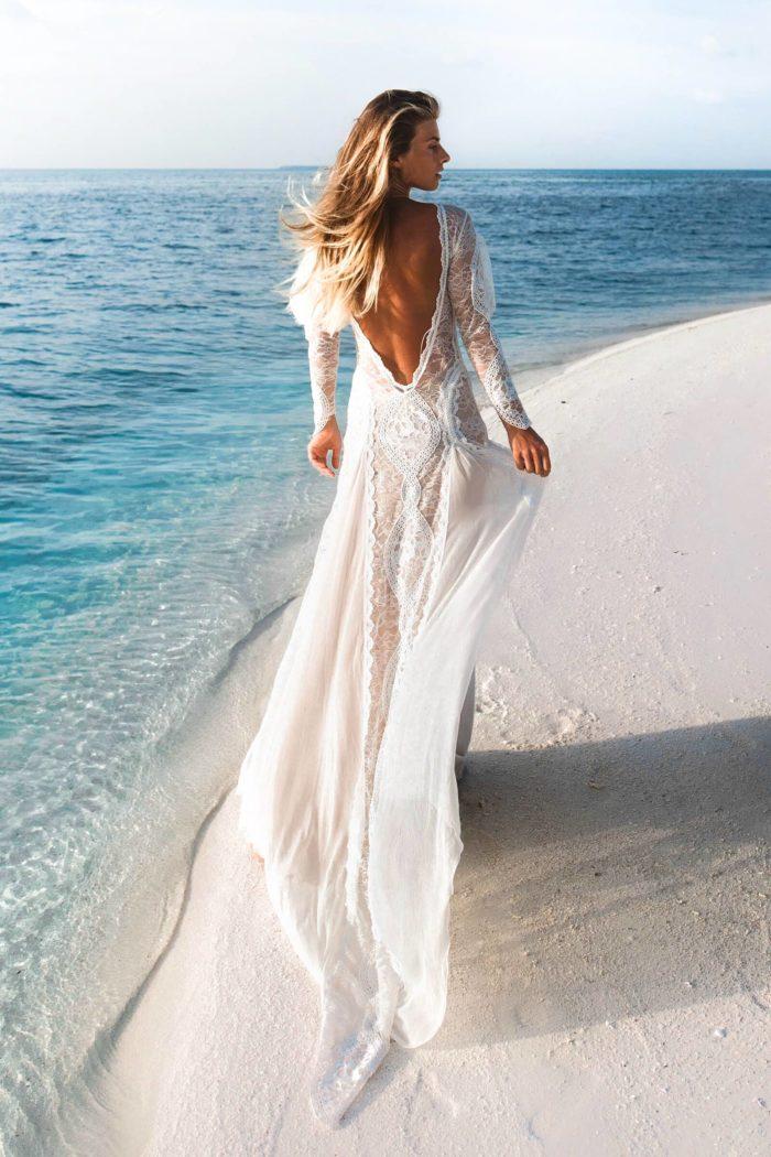 Back shot of bride wearing Grace Loves Lace Inca Gown walking along beachfront