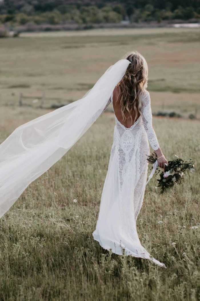 Back shot of bride wearing Grace Loves Lace Inca Gown holding bouquet in field