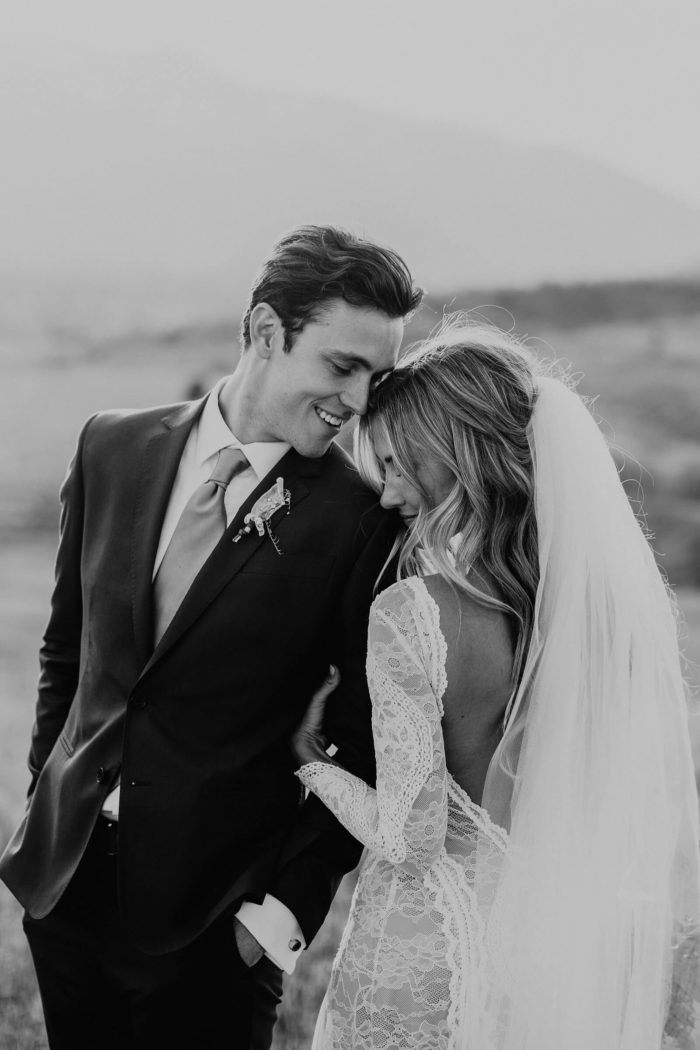 Black and white shot of bride wearing Grace Loves Lace Inca Gown standing with groom