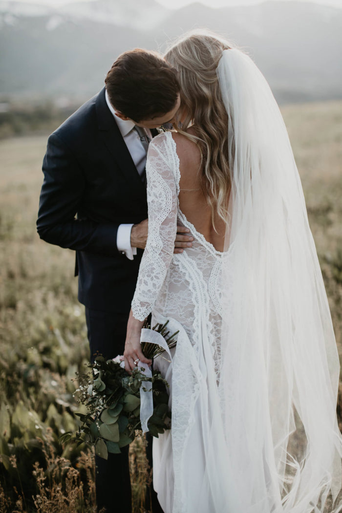 Bride wearing Grace Loves Lace Inca Gown kissing groom holding bouquet