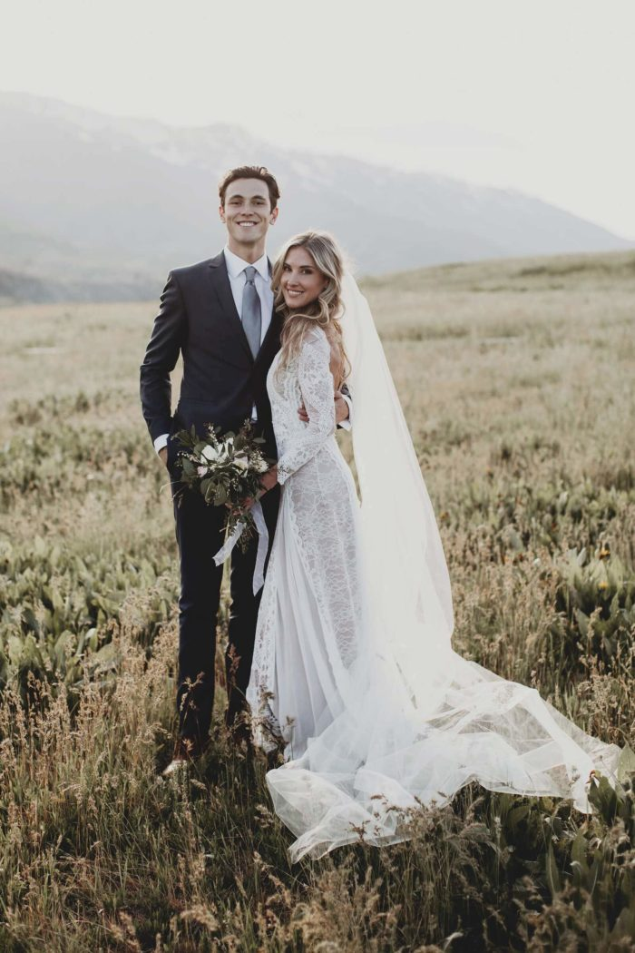 Bride wearing Grace Loves Lace Inca Gown standing with groom holding bouquet