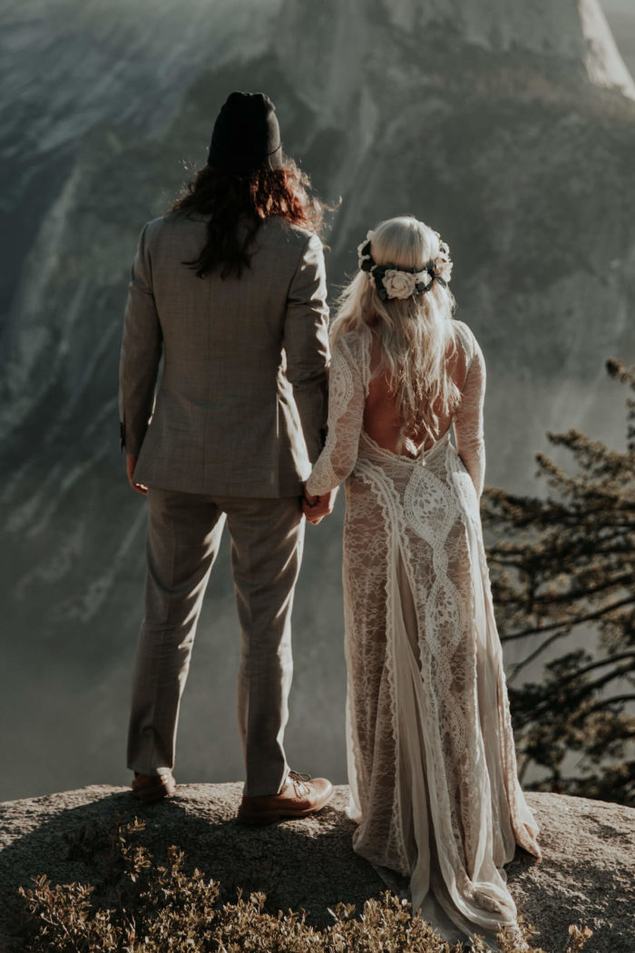 Back shot of bride wearing Grace Loves Lace Inca Gown holding hands with groom on mountainside