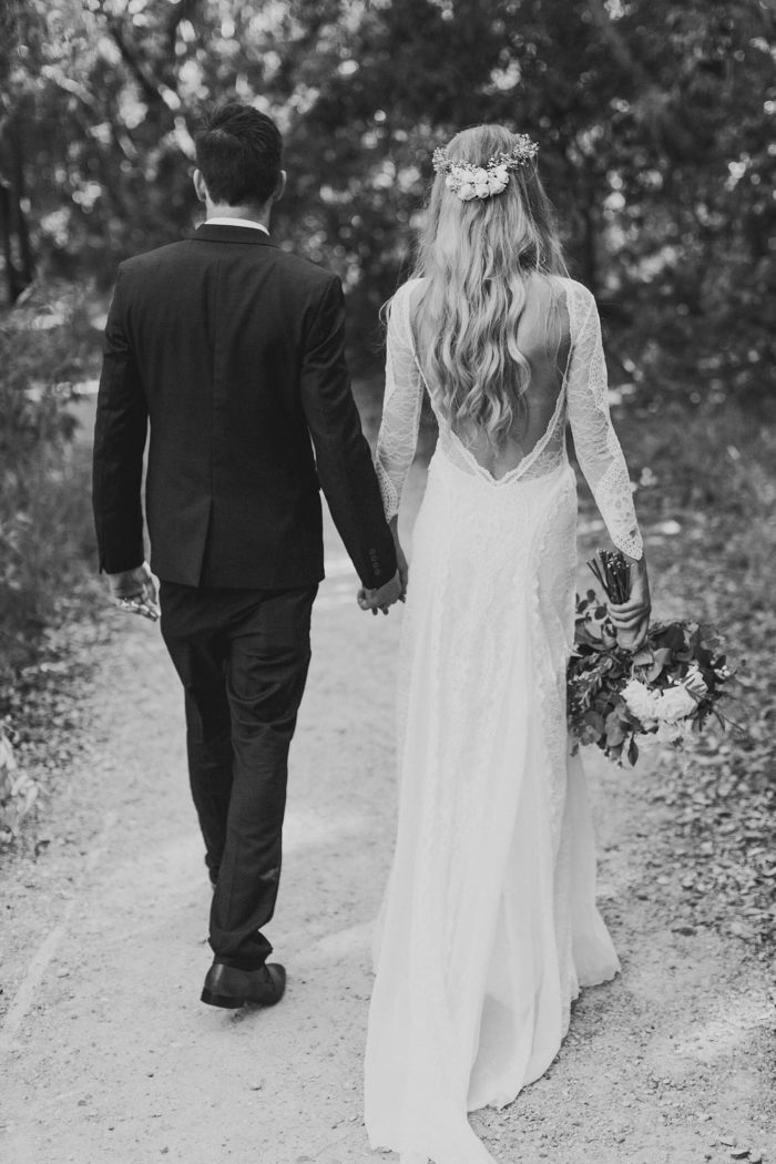 Black and white shot of bride wearing Grace Loves Lace Inca Gown holding hands with groom holding bouquet