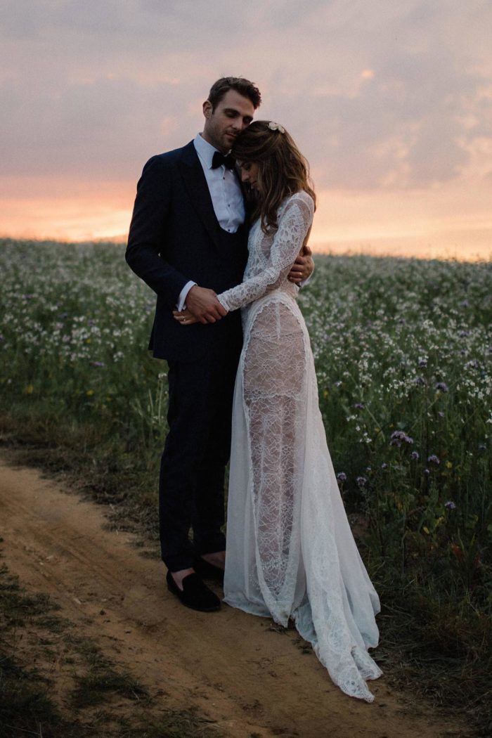 Bride wearing Grace Loves Lace Inca Gown embracing groom in field of flowers