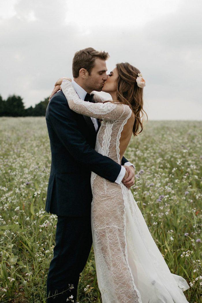 Bride wearing Grace Loves Lace Inca Gown kissing groom in field of flowers