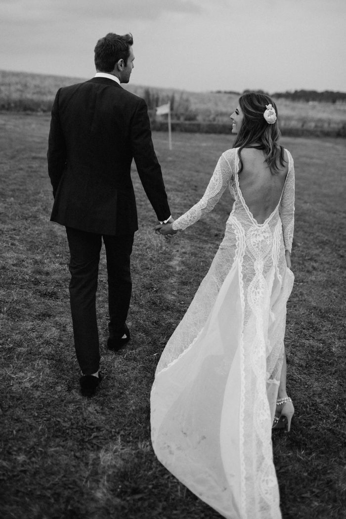 Black and white shot of bride wearing Grace Loves Lace Inca Gown holding hands with groom