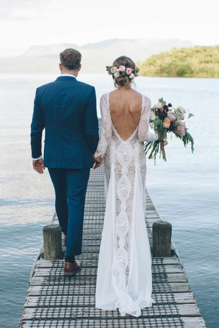 Bride wearing Grace Loves Lace Inca Gown holding hands with groom holding bouquet on waterside pier