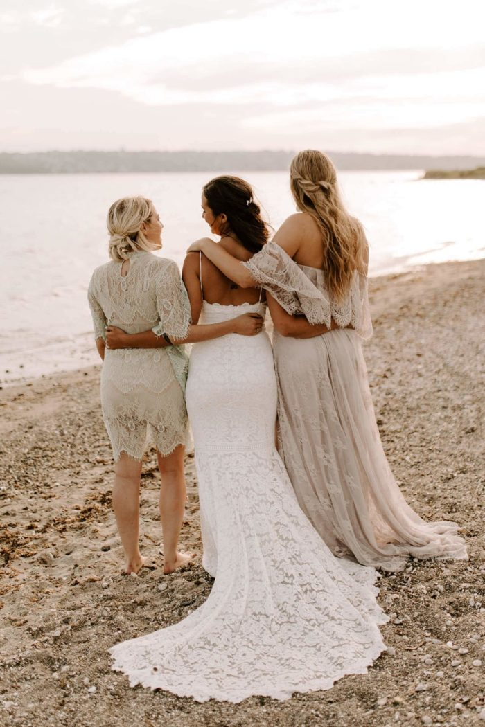 Bride wearing Grace Loves Lace Hart Gown standing with bridesmaids on beach