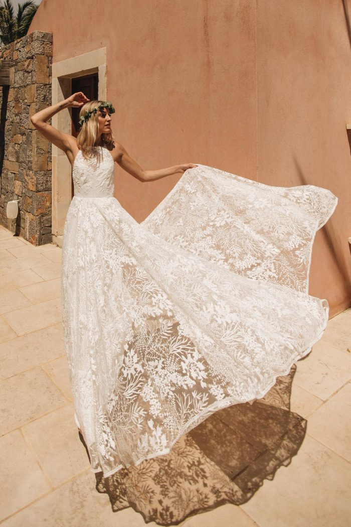 Blonde bride wearing Grace Loves Lace Harri Gown holding skirt that blows in wind in hand