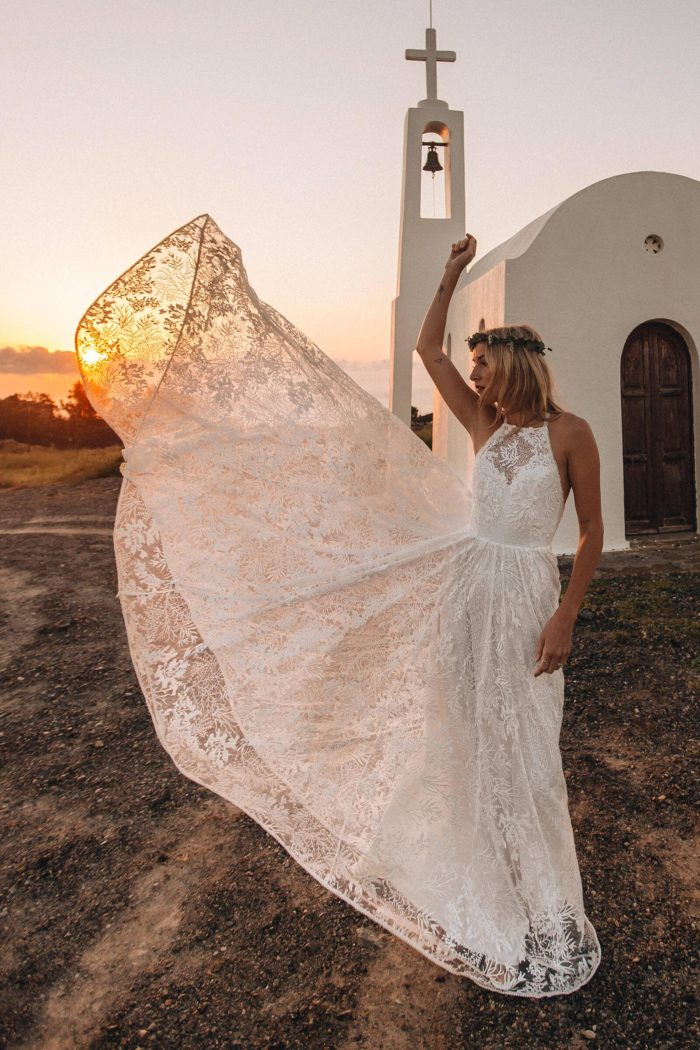 Blonde bride wearing Grace Loves Lace Harri Gown with skirt blowing in wind at sunset