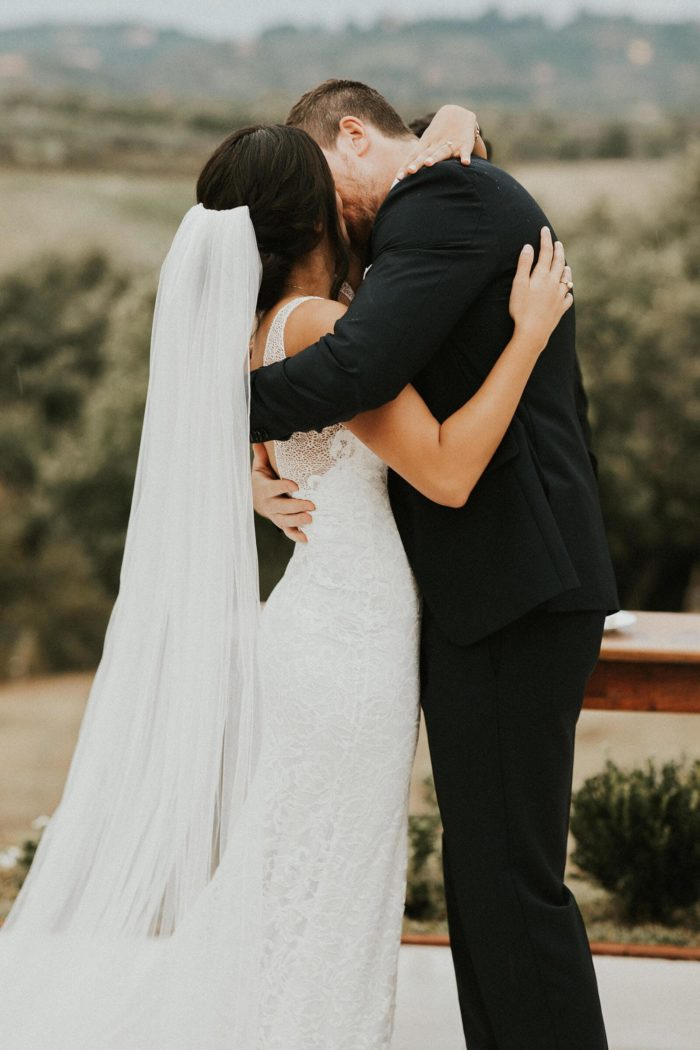 Brunette bride wearing Grace Loves Lace Gia Gown kissing groom