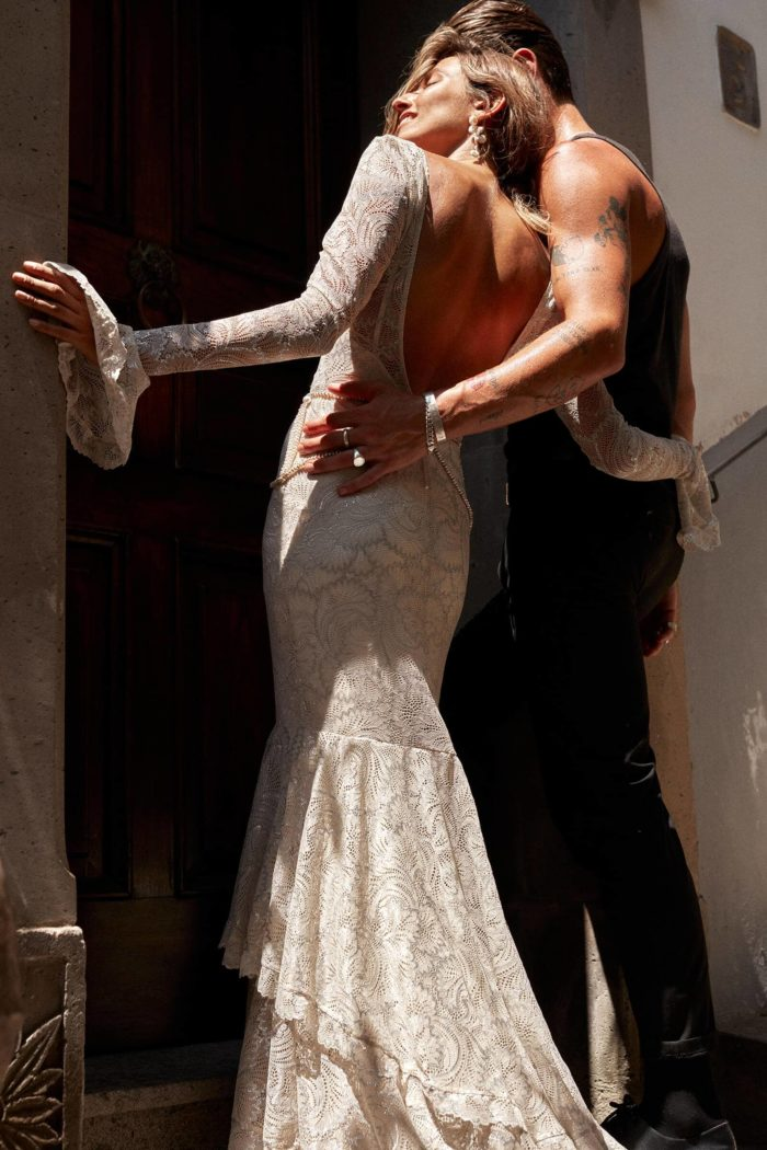 Back shot of bride wearing Grace Loves Lace Farrow Gown standing in doorway with groom's hand on waist