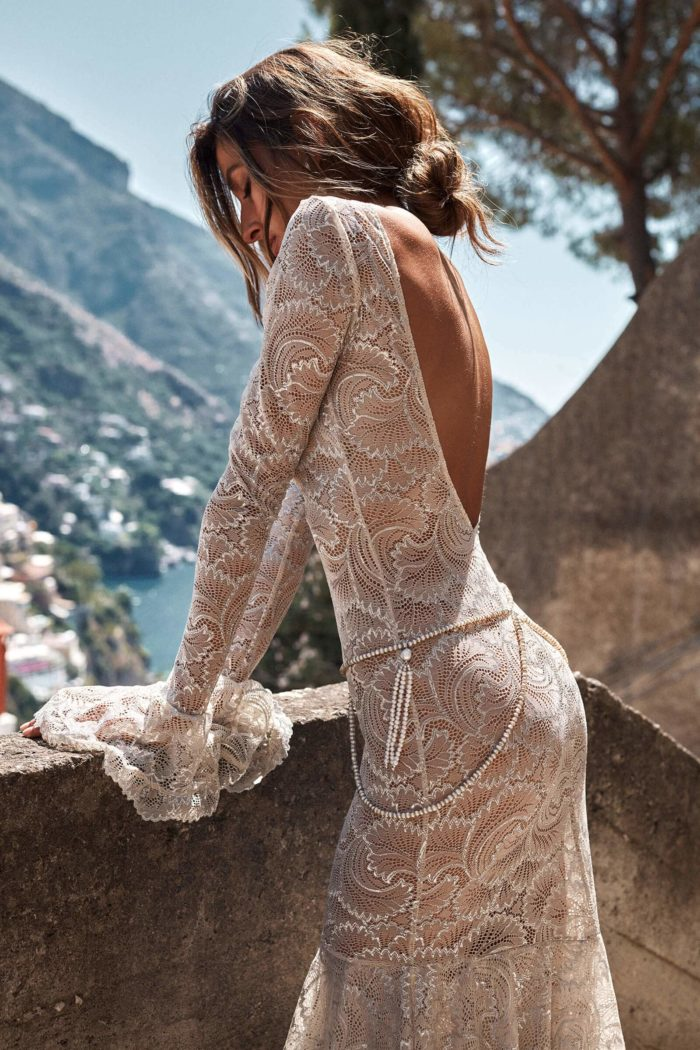 Brunette bride wearing Grace Loves Lace Farrow Gown leaning on low stone wall with eyes closed