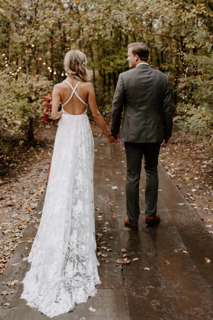 Blonde bride wearing Grace Loves Lace Megan Gown holding hands with groom on damp garden pathway