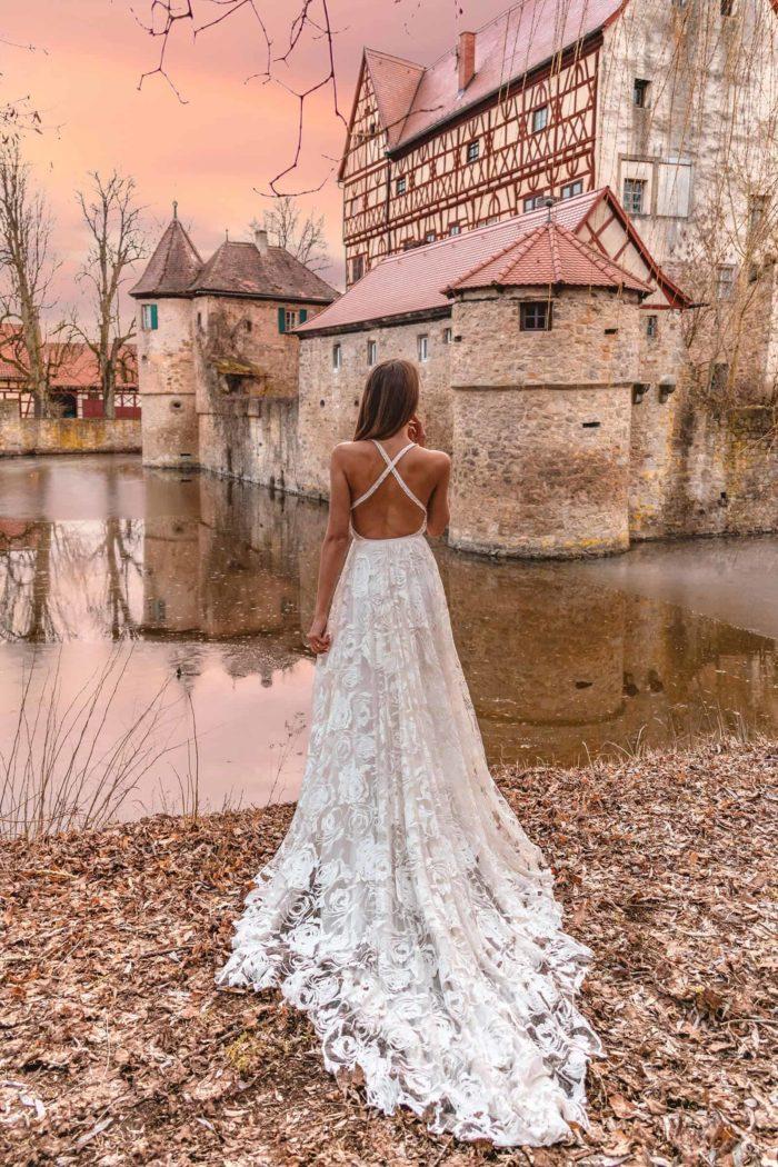 Back shot of brunette bride wearing Grace Loves Lace Megan Gown behind aged building