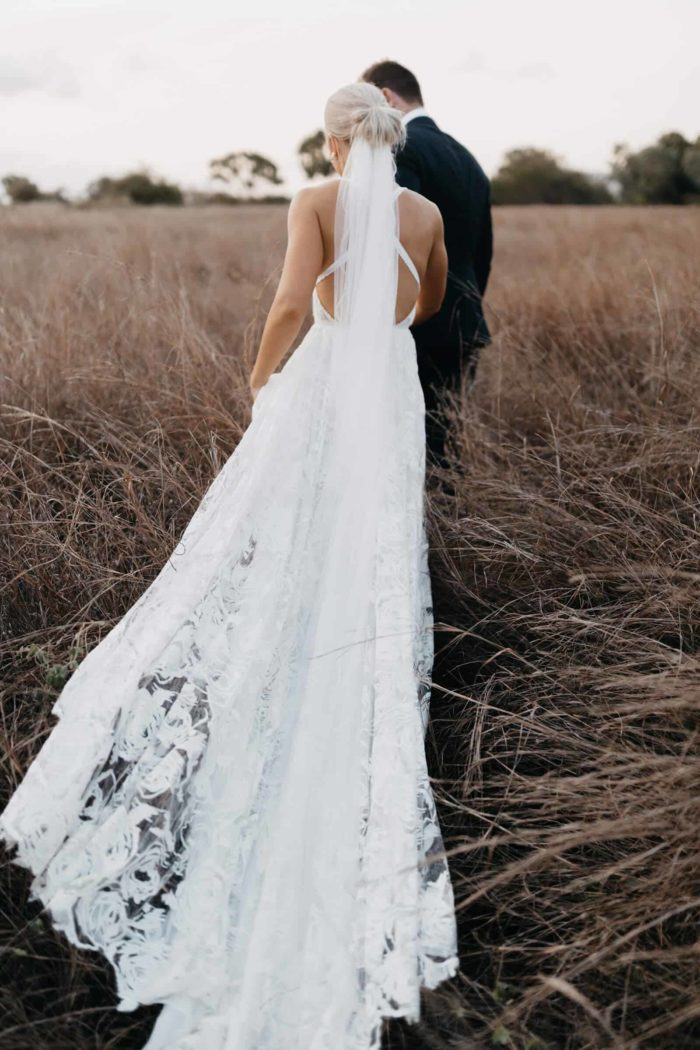 Back shot of blonde bride wearing Grace Loves Lace Megan Gown being led by groom through grassy field