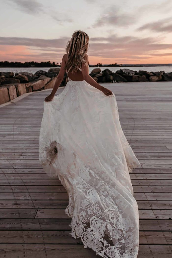 Back shot of blonde bride wearing Grace Loves Lace Megan Gown holding skirt in both hands near ocean