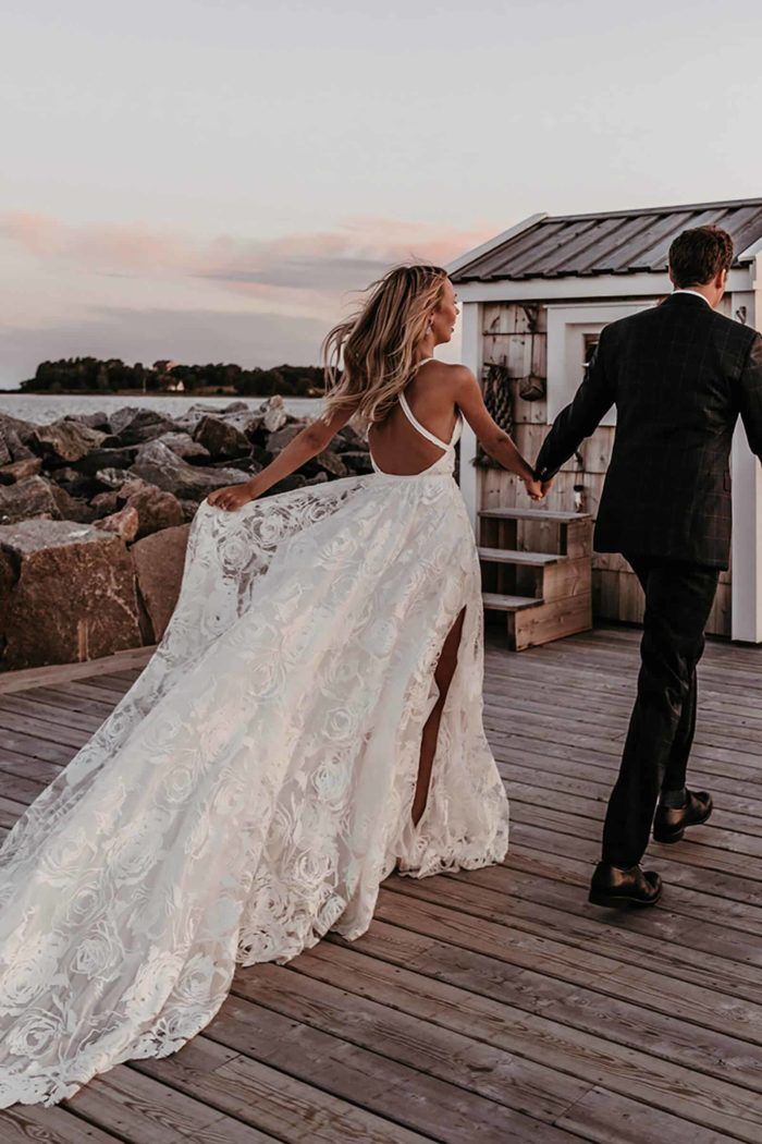 Blonde bride wearing Grace Loves Lace Megan Gown while being led by groom along seaside path