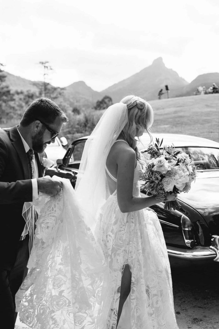 Black and white shot of bride wearing Grace Loves Lace Megan Gown holding bouquet in front of classic car