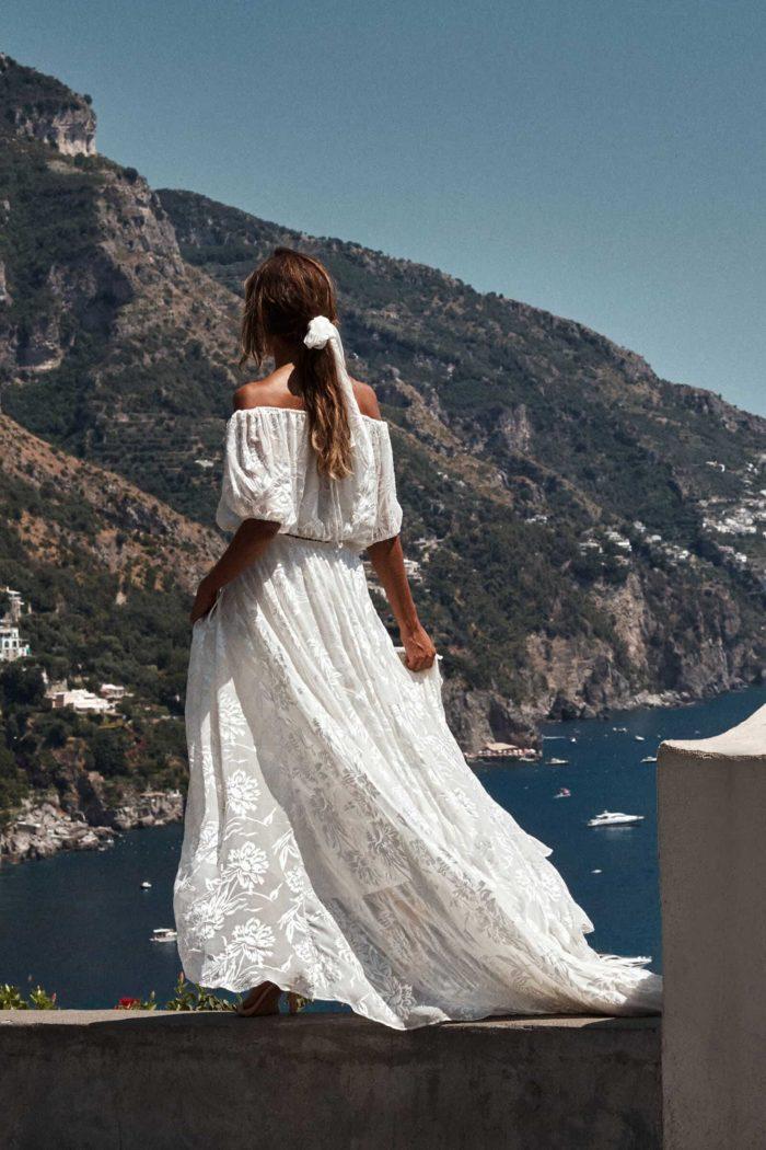 Back shot of bride wearing Grace Loves Lace Loyola Set holding skirt