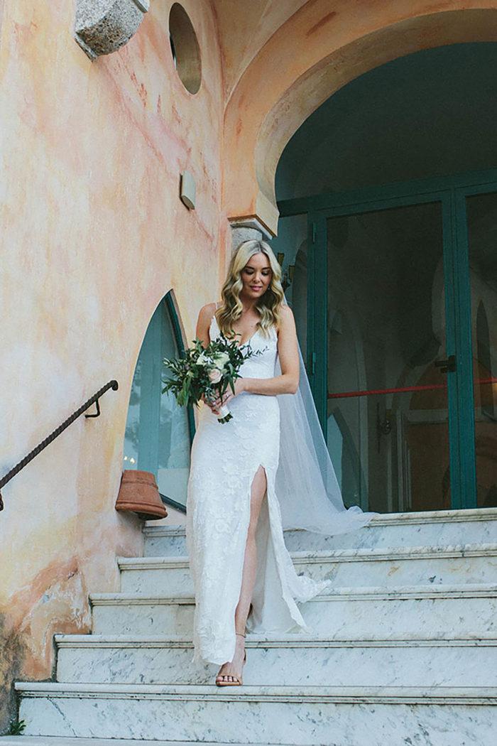 Blonde bride wearing Grace Loves Lace Lottie Gown holding bouquet walking down stairs