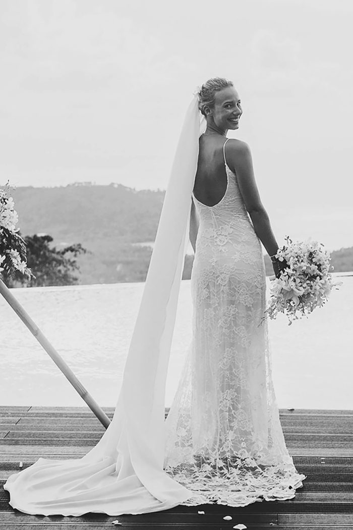 Black and white back shot of bride wearing Grace Loves Lace Lottie Gown holding bouquet