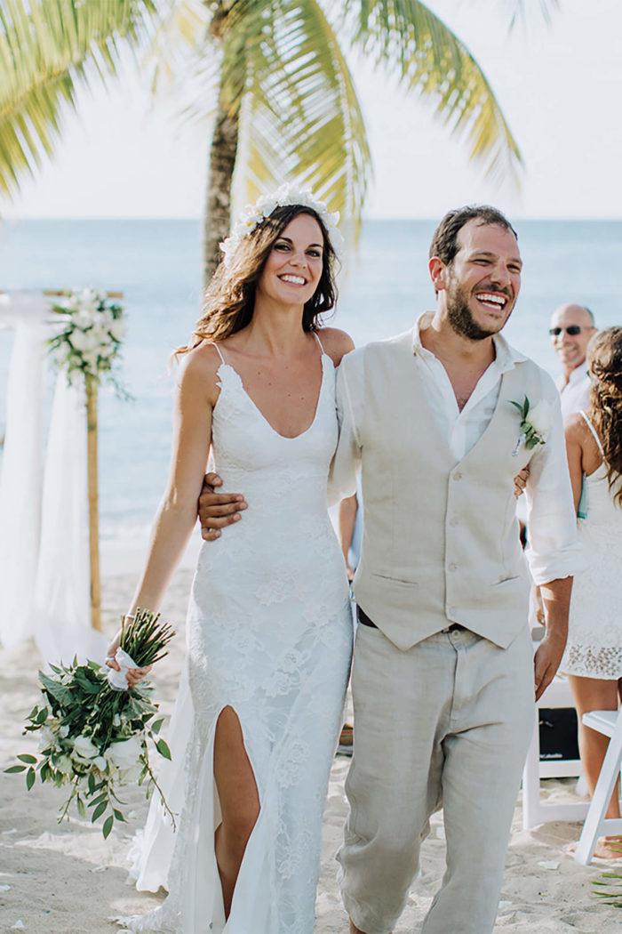 Brunette bride wearing Grace Loves Lace Lottie Gown holding bouquet walking with groom