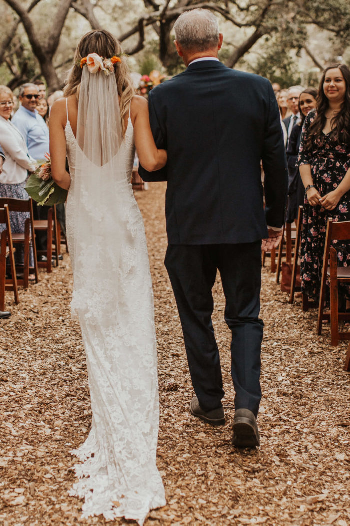 Back shot of bride wearing Grace Loves Lace Lottie Gown walking down aisle with father