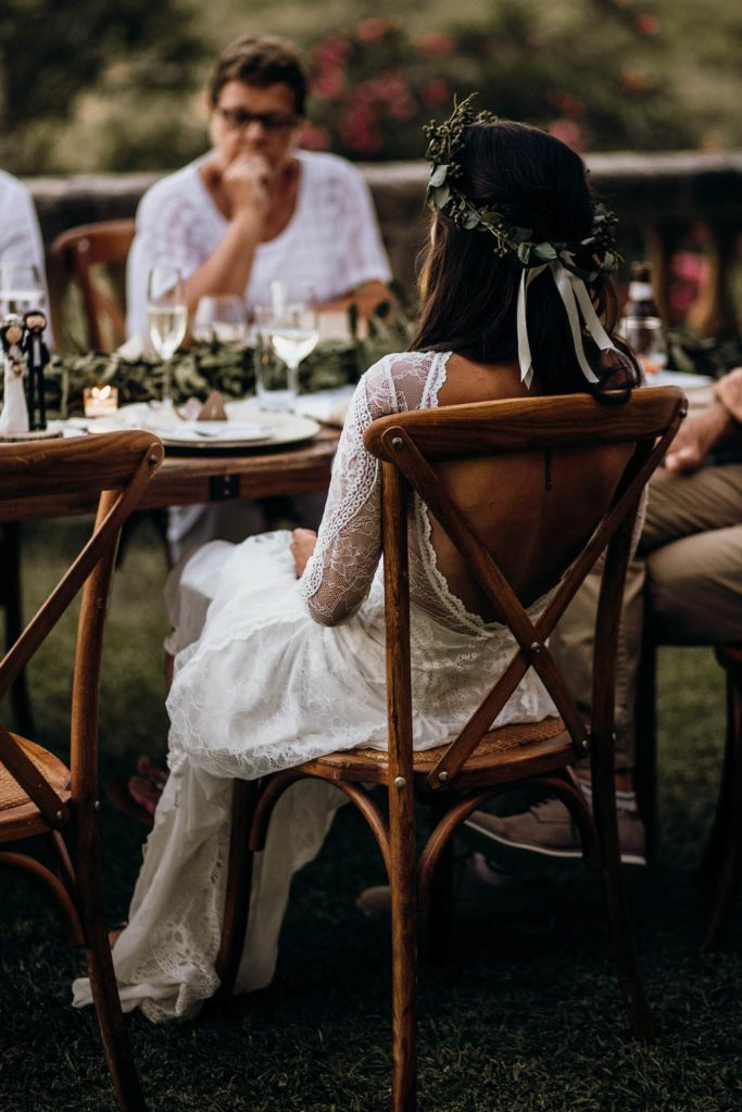 Back shot of bride wearing Grace Loves Lace Inca Gown sitting in dining chair