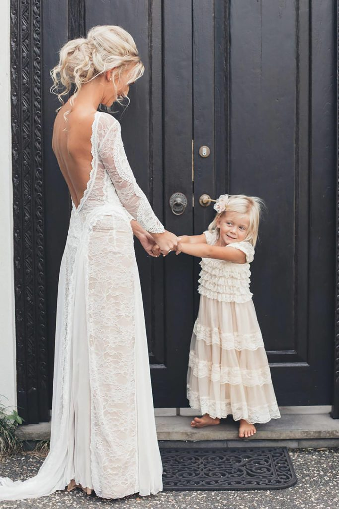 Bride wearing Grace Loves Lace Inca Gown holding hands with flower girl