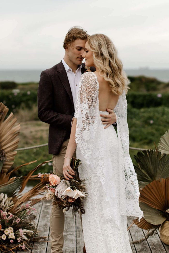 Bride wearing Grace Loves Lace Verdelle 2.0 Gown embracing groom