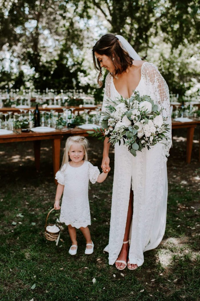 Bride wearing Grace Loves Lace Verdelle 2.0 Gown holding hands with flower girl