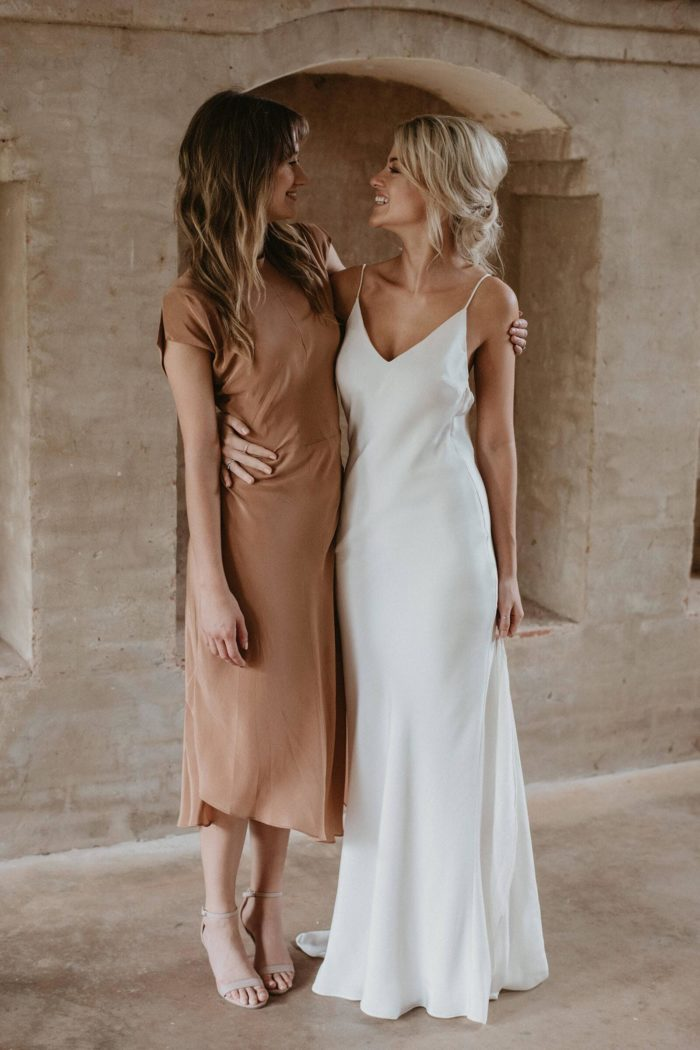 Bride wearing Grace Loves Lace Summer Gown standing with bridesmaid