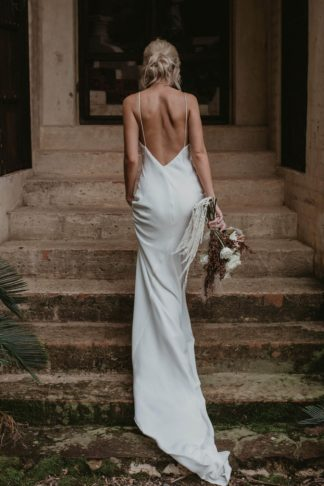 Back shot of bride wearing Grace Loves Lace Summer Gown holding bouquet