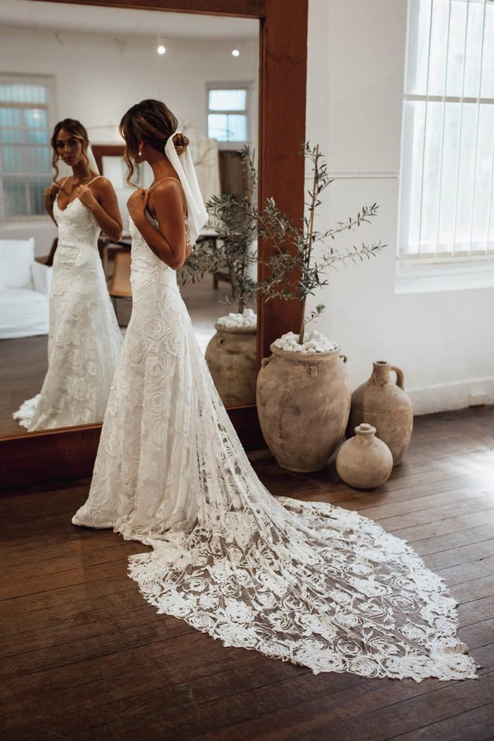 Side shot of bride wearing Grace Loves Lace Rosa Gown in front of mirror