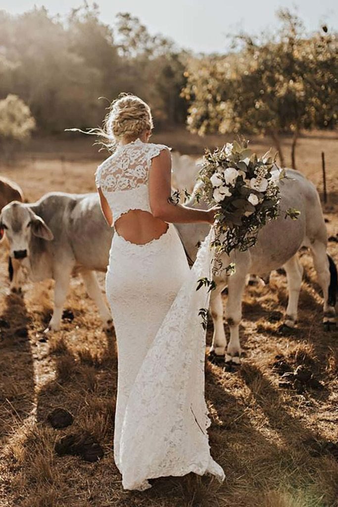 Back shot of blonde bride wearing Grace Loves Lace Renata Gown holding bouquet near cows