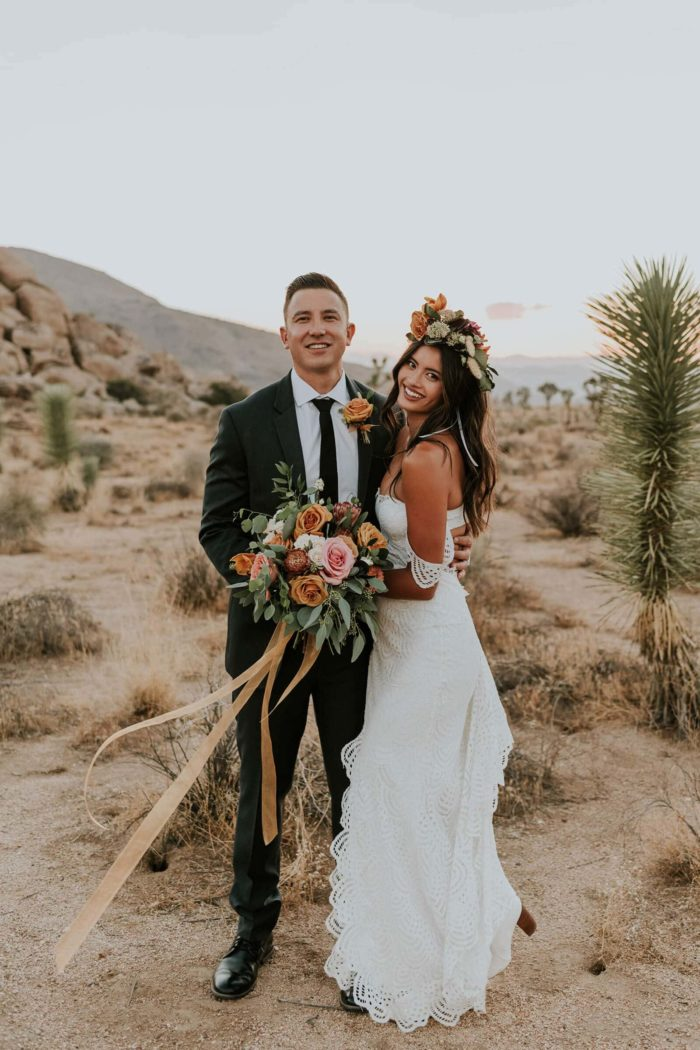 Brunette bride wearing Grace Loves Lace Paloma Gown being held by groom holding bouquet in desert area