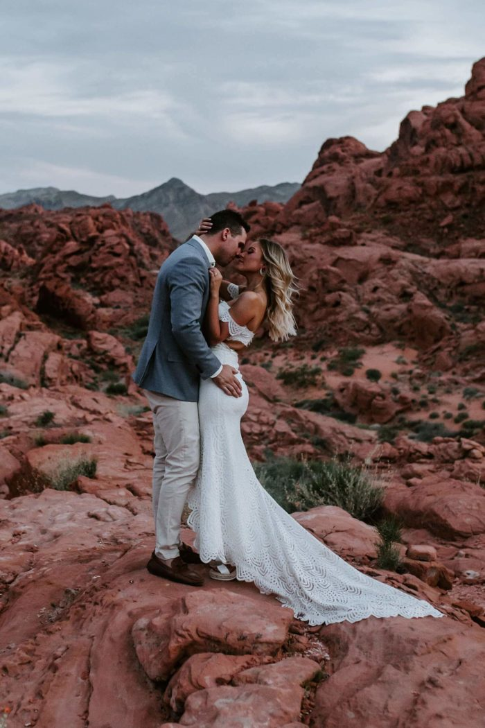 Blonde bride wearing Grace Loves Lace Paloma Gown embracing groom in red rocky area