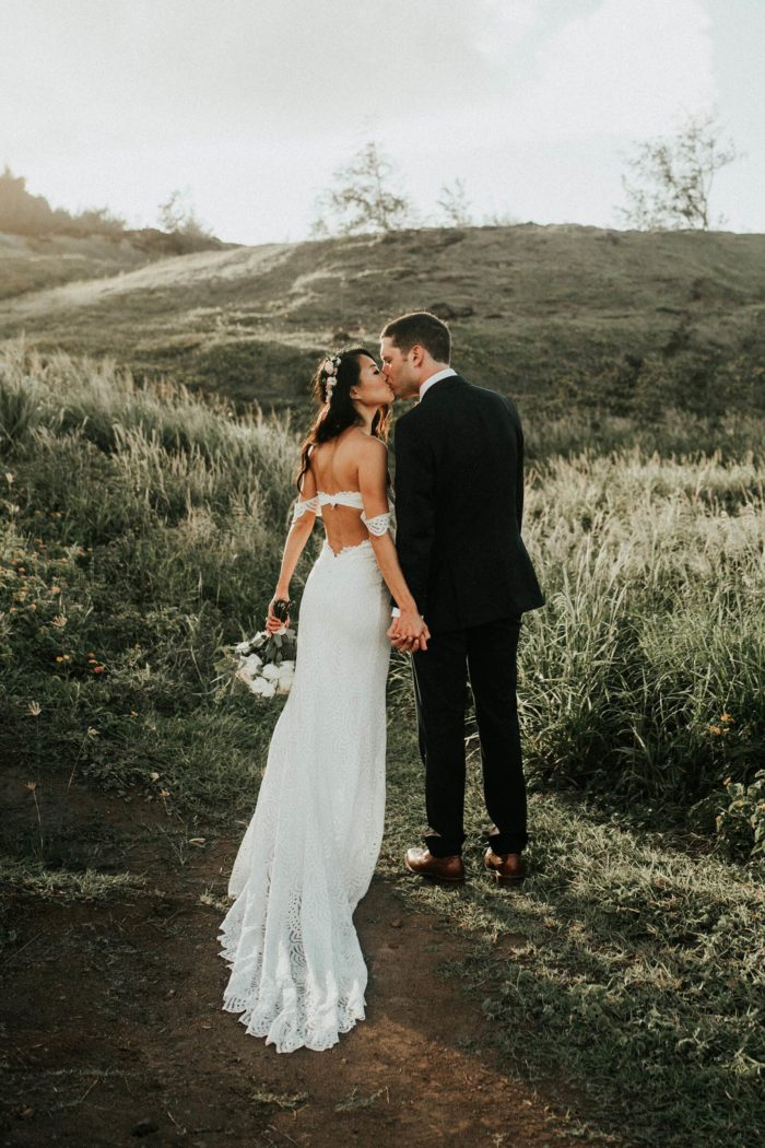 Brunette bride wearing Grace Loves Lace Paloma Gown kissing groom holding bouquet in grassy field