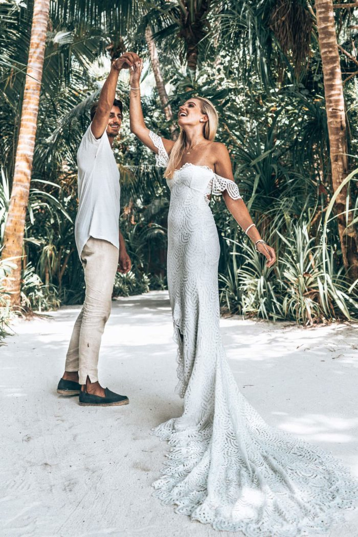 Blonde bride wearing Grace Loves Lace Paloma Gown dancing with groom on sandy beach with palm trees