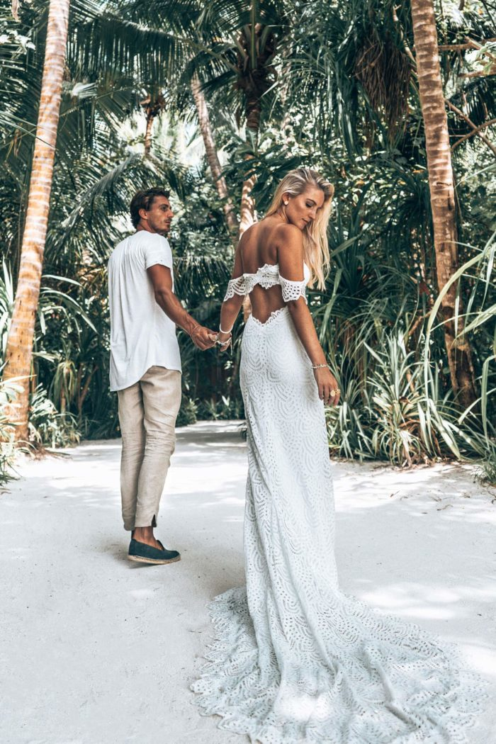 Back shot of blonde bride wearing Grace Loves Lace Paloma Gown holding hands with groom on beach