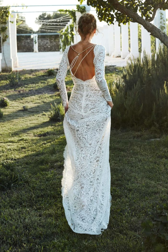 Back shot of bride wearing Grace Loves Lace Orla Gown holding skirt in both hands