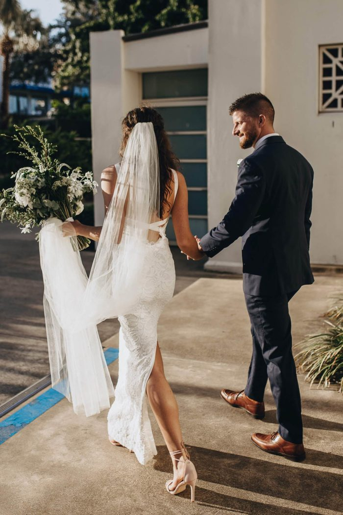Back shot of bride wearing Grace Loves Lace Nia 2.0 Gown holding bouquet holding hands with groom