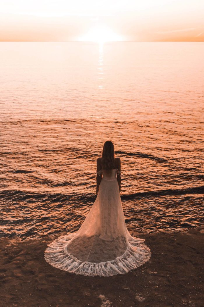 Back shot of bride wearing Grace Loves Lace Fabienne 2.0 Gown on beach at sunset