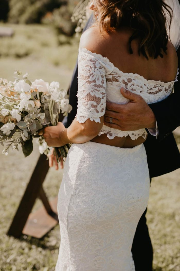 Brunette bride wearing Grace Loves Lace Everly Gown holding bouquet being held by groom