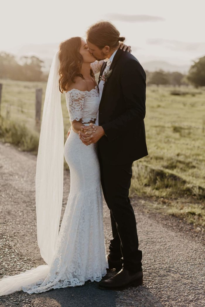 Blonde bride wearing Grace Loves Lace Everly Gown kissing groom