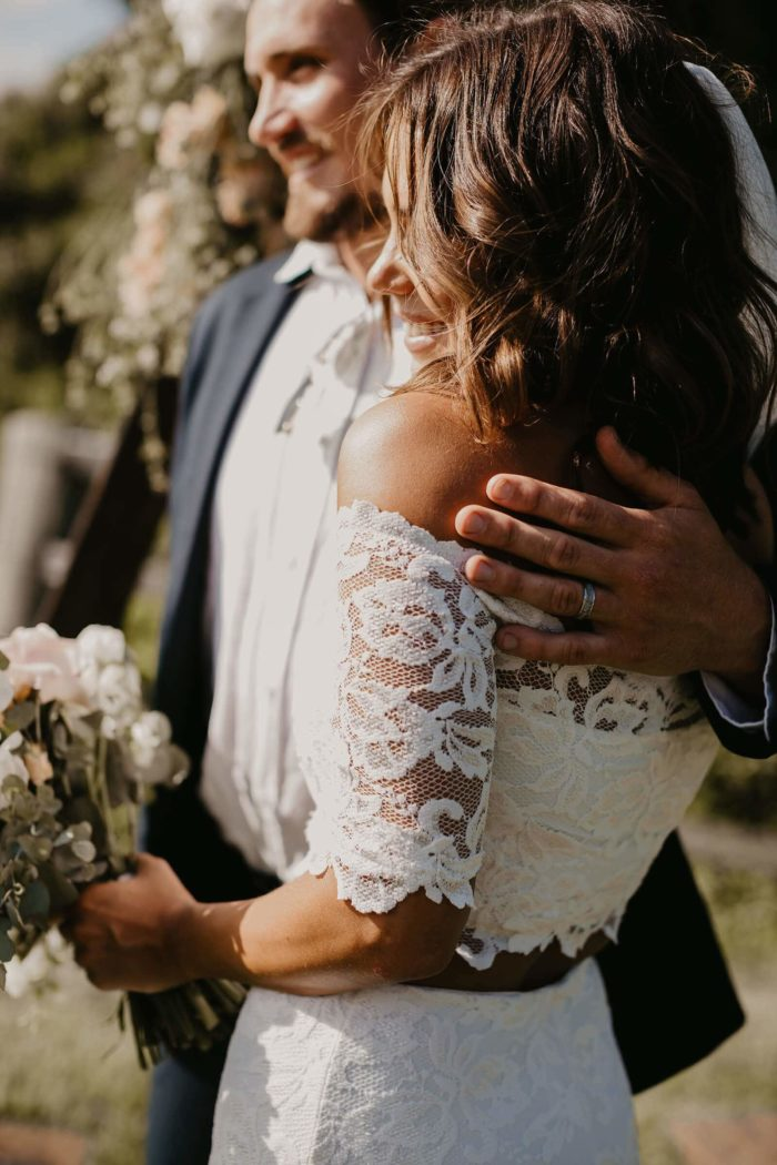 Brunette bride wearing Grace Loves Lace Everly Gown being held by groom