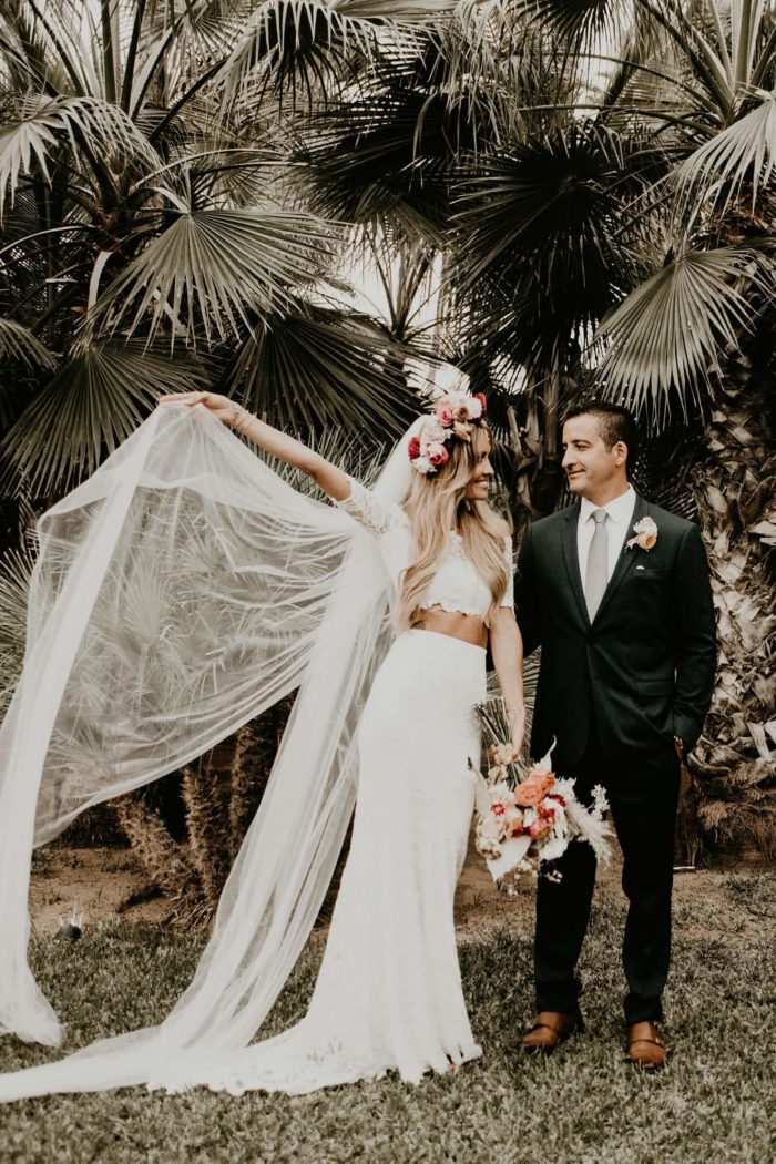 Blonde bride wearing Grace Loves Lace Everly Gown holding veil in one hand standing with groom